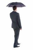 Businessman walking and holding umbrella Stock Images