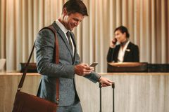 Businessman in hotel hallway with cellphone and luggage. Businessman walking in hotel lobby with suitcase and using his smart phone. Male business traveler in Royalty Free Stock Photos