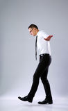 Businessman walking on invisible rope. On gray background Stock Photography