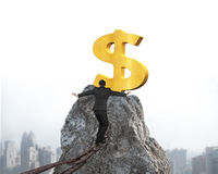Businessman walking on iron chain toward dollar sign with citysc Royalty Free Stock Photography