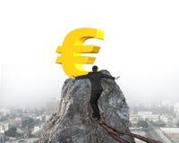Businessman walking on iron chain toward euro symbol with citysc Royalty Free Stock Photos
