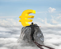 Businessman walking on iron chain toward euro symbol with clouds Royalty Free Stock Image