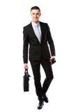 Businessman walking with laptop bag and umbrella Stock Photo