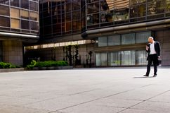 Businessman walking and looking at his cellphone Royalty Free Stock Images