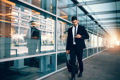 Businessman walking with luggage and using mobile phone at airpo Royalty Free Stock Images