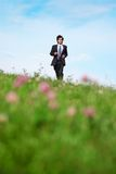 Businessman walking on meadow stock photography