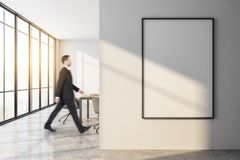 Businessman walking in modern meeting room. Side view of attractive european businessman walking in modern white meeting room interior with empty poster on wall stock images