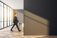 Businessman walking in modern meeting room. Side view of attractive european businessman walking in modern meeting room interior with copy space on wall. Worker stock image