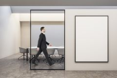Businessman walking in modern meeting room. Side view of attractive european businessman walking in modern white meeting room interior with empty banner on wall royalty free stock photos