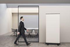 Businessman walking in modern meeting room. Side view of attractive european businessman walking in modern white meeting room interior with empty billboard on stock image