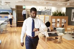 Businessman Walking Through Modern Office Checking Health Data On Smart Watch stock images