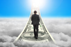 Businessman walking on the money stairs with sky sunlight clouds Stock Images