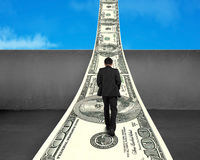 Businessman walking on money way over concrete wall Royalty Free Stock Photos