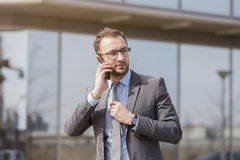 Businessman walking next to the business building and talking on stock photo
