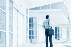 Businessman walking through office building. Stock Images