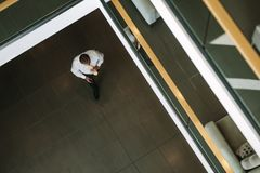 Businessman walking through office lobby Stock Photography