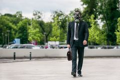 Businessman walking outdoor with briefcase wearing a gas mask. On face Stock Photos