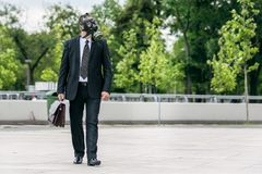 Businessman walking outdoor wearing a gas mask on the face. Businessman walking outdoor with briefcase wearing a gas mask on the face Stock Photography