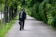Businessman walking outdoor wearing a gas mask on the face. Businessman walking outdoor with briefcase wearing a gas mask on the face Royalty Free Stock Images