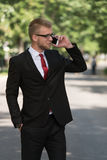 Businessman Walking Outdoors In Park While Using Mobilephone Stock Photos