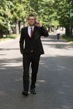 Businessman Walking Outdoors In Park While Using Mobilephone Stock Photography