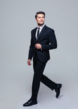 Businessman walking over gray background Royalty Free Stock Photos