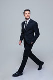 Businessman walking over gray background Stock Images