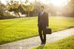 Businessman walking at the park Stock Photos