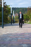 businessman walking in a park Stock Photography