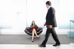 Businessman walking past businesswoman sitting in chair in office lobby (blurred motion) Stock Image