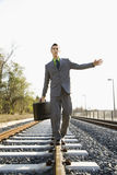 Businessman Walking on Railroad Tracks Stock Image