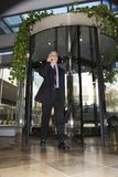 Businessman walking through revolving door. Royalty Free Stock Images