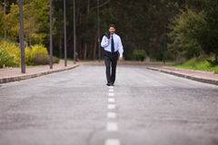 Businessman walking on the road Royalty Free Stock Photography