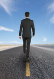 Businessman walking on road Stock Images