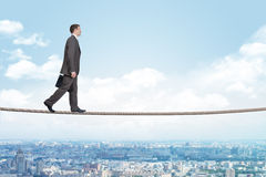 Businessman walking on rope Stock Photos