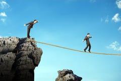 Businessman walking on rope above gap Stock Image