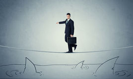 Businessman walking on rope above sharks Royalty Free Stock Photos
