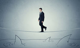 Businessman walking on rope above sharks Stock Images