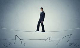 Businessman walking on rope above sharks Stock Image