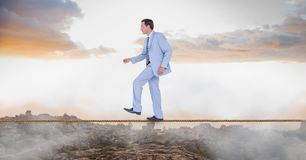 Businessman walking on rope over landscape. Digital composite of Businessman walking on rope over landscape Royalty Free Stock Photo