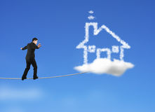 Businessman walking on rope toward house shape cloud in sky Stock Photo