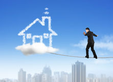 Businessman walking on rope toward house shape cloud with skyscr Royalty Free Stock Photography