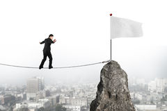 Businessman walking on rope toward white flag with cityscape Stock Image