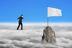 Businessman walking on rope toward white flag with cloudscape Royalty Free Stock Photography