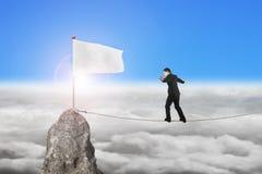 Businessman walking on rope toward white flag with sunlight Stock Photo