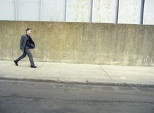 Businessman Walking On Sidewalk Royalty Free Stock Photo