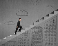 Businessman walking on stairs with modern building doodles. On wall Stock Photos