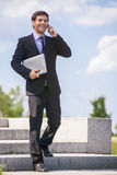 Businessman walking on stares outside and smiling. Royalty Free Stock Photo