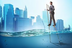 The businessman walking on stilts in water sea royalty free stock image