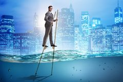 The businessman walking on stilts in water sea royalty free stock images